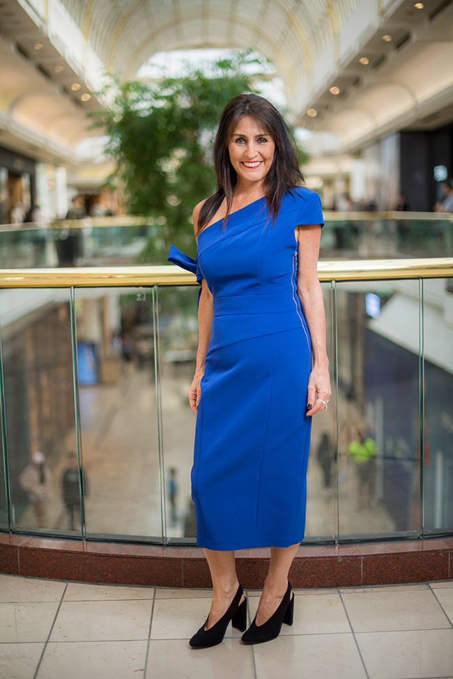 Cindy wearing a blue Cue dress