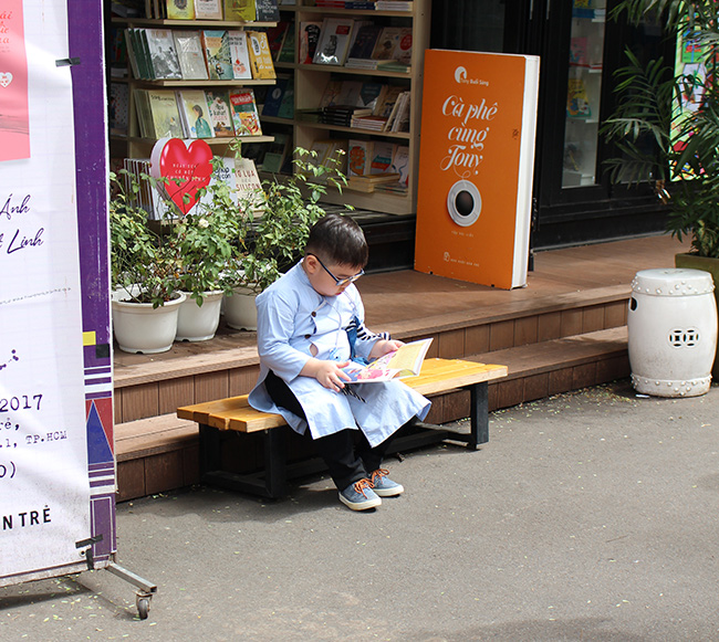 Young Vietnamese boy reading in Saigon street