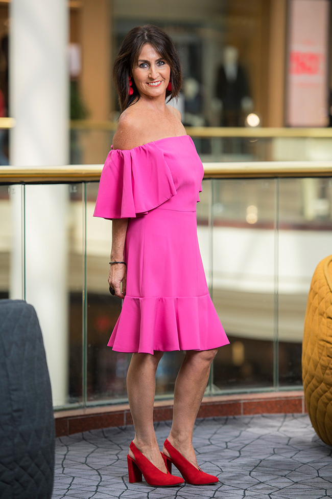 Cindy wearing a structured off the shoulder ruffle dress in fuschia