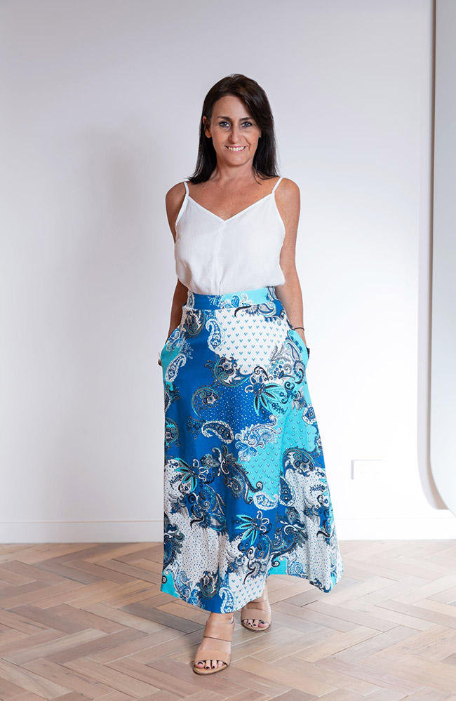 Cindy wearing a gorgeous pattern blue skirt giving a summer vibe, with a fresh white silk tank elevating the whole look.